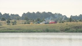 Smoke from fire in camp with tents and car on river bank. Smoke coming out of fire in a camp consisting of three tents and old minibus on river bank in the stock video