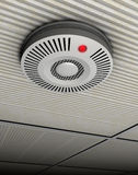 Smoke and fire detector. Illustration of a smoke and fire detector in gray at a gray ceiling Royalty Free Stock Image