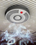 Smoke and fire detector. Illustration of a smoke and fire detector in rising smoke at a gray ceiling Royalty Free Stock Image