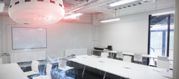 Composite image of smoke and fire detector. Smoke and fire detector against classroom Royalty Free Stock Photos