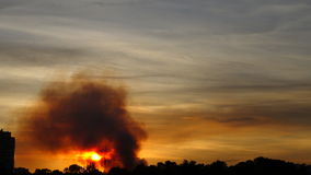 The smoke from the fire over the city, time lapse video. Sunset stock footage