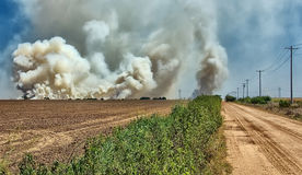 Smoke and Fire at the Ranch. A prairie fire sends up smoke clouds at a rural ranch location in the country Stock Photo