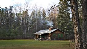 Smoke from fireplace rises from the chimney of a cozy rustic cabin. Smoke from fireplace rises from the chimney of a cozy rustic hunting cabin in the woods royalty free stock photos