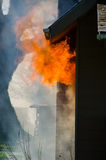 Smoke and Flames. Licks of flame burst out of the window of a house surrounded by thick black smoke stock photography