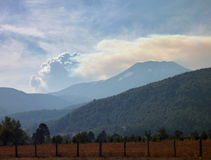 Smoke from forest fire over the hill Stock Photography
