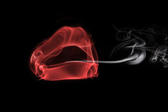 Smoke in the form of female lips. Smoking a cigarette Royalty Free Stock Image