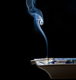 Smoke fume and cigarette. Cigarette on ashtray with a beautiful wisp of smoke Royalty Free Stock Photo