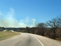 Smoke from a grass or forest fire along highway in eastern Oklahoma. Billowing smoke is visible from the highway as grass and forest fires burn in the extremely Royalty Free Stock Images