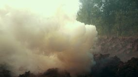 Smoke grenade on battle field. Smoke bomb on military background. Smoke grenade exploded on battle field. Smoke bomb for disguise on military background stock footage