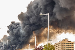 The smoke of a huge fire flooding the sky of a city Royalty Free Stock Image