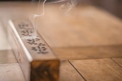Smoke from incense burner. Close up of incense burner on solid oak table top Stock Photography