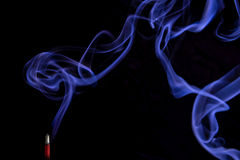 Smoke, Incense Stick. Blue smoke swirling from the red incense stick against the black background royalty free stock photography
