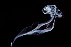Smoke, Incense Stick. Blue smoke swirling from the blue incense stick against the black background Stock Photography