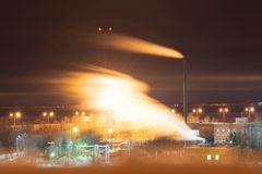 Factory chimney piping smoke or steam into the air pollution. motion of smoke with blur. Smoke from industrial pipe plant at night. air pollution. motion of royalty free stock images