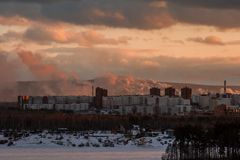 Smoke from the industrial plant over the city in the clouds. Factory smoke tubes. Royalty Free Stock Images