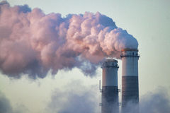 Smoke from an industrial smokestack. Lit by the Central Florida sunrise, smoke pours from the stacks of a coal-fired electrical power generation plant. This stock image