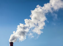 Smoke from industrial smokestack on a clear blue sky Royalty Free Stock Images