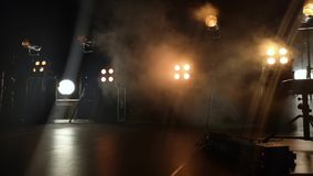 Close-up video of a concert stage and lighting fixtures on it. Smoke from a smoke installation gently breaks yellow light and crea