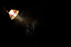 Smoke in the light of a bulb. The smoke from a cigarette flies by under a lamp Royalty Free Stock Images