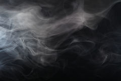 Smoke in the light. On a dark background Stock Image