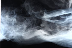 Smoke in the light. On a dark background Royalty Free Stock Image