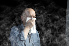 Smoke. A man cover his mouth with an hand for the smoke Royalty Free Stock Photos