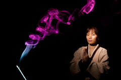 Smoke and the meditating woman. Stock Photos
