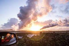 Smoke out of geothermal pipes against dramatic sunset sky. Shot out of a car, urbanization and global warming, roadtrip in Iceland Royalty Free Stock Images
