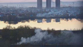 Smoke over the city. Landscape of the city in the smoke from the houses chimney and view of the lake and the construction of high buildings stock video