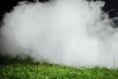Smoke over the green grass lawn Stock Photo
