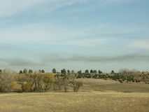 Smoke over pasture. Country pasture with smoke stream overhead Royalty Free Stock Photos