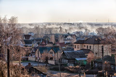 Smoke over the town. Smoke from the burned leaves over the small city Stock Image