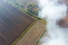 The smoke over the village. Clubs of smoke over the village houses and fields. Aerophotographing. Areas stock photography