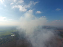 The smoke over the village. Clubs of smoke over the village houses and fields. Aerophotographing areas.  stock photography