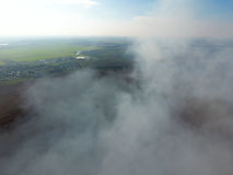 The smoke over the village. Clubs of smoke over the village houses and fields. Aerophotographing areas.  royalty free stock photo