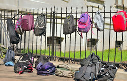 School bags hanging on a lattice. Handbags of students hanging on metal fence Stock Photos