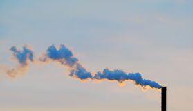 Smoke from pipes. The smoke from a pipe is illuminated by the sun at sunset Royalty Free Stock Image