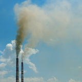 Smoke from the pipes against blue sky Royalty Free Stock Image