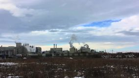 Smoke from plant against the blue sky with clouds. Winter landscape with partially snow-covered field. stock video footage