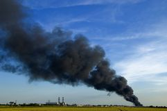 Smoke plume. Huge plume of black smoke from fire rising high of flat land against blue sky