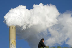 Smoke plume of power plant and cyclist. Netherlands, province of Gelderland. The chimney pipe of the Electrabel plant, power plant Gelderland. This factory is Royalty Free Stock Image