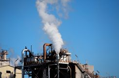 Smoke pollution billowing from industrial building. Or refinery Stock Photos