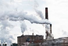 Smoke pollution through industrial chimneys royalty free stock photos