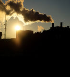 Smoke from power plant chimney at sunset backlit toned image Stock Photos