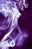 Smoke on Purple. The graceful swirls of smoke from burning insence illuminated with purple color Royalty Free Stock Photography