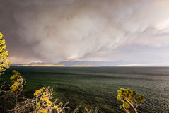 Firestorm in Yellowstone. Smoke resembling a thundercloud billows from a nearby forest fire as the wind drives the wildfire toward the shoreline of Lake Royalty Free Stock Images