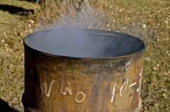 Smoke rises from old burn barrel Royalty Free Stock Photography