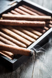 Smoke rising from a burning cigar Stock Photo