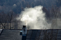 Smoke rising from a chimney. Of old house stock photography
