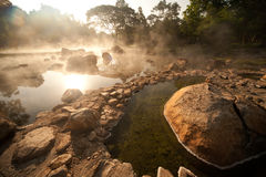 Smoke rising from hot springs in Northern of Thailand. Royalty Free Stock Photography